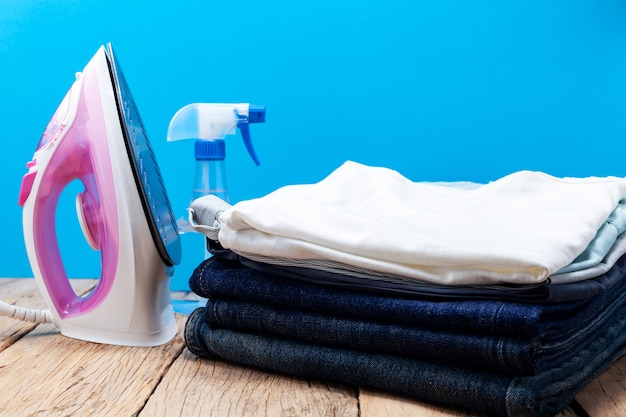Iron and stack of jeans and t-shirt clothes on wooden plank, blue background Premium Photo