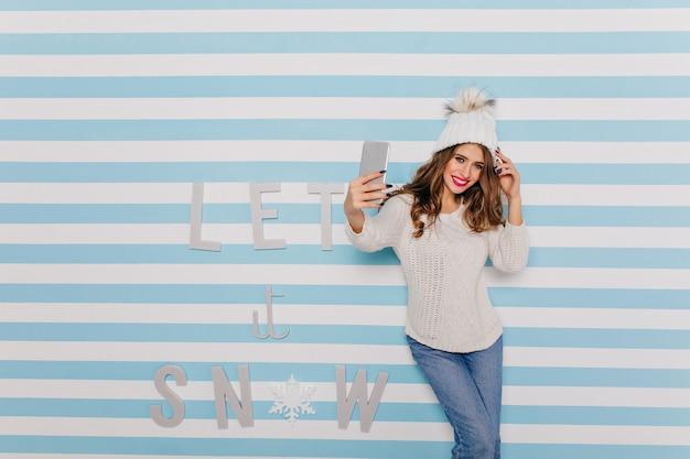 灰色の携帯電話でポーズをとるピンクの赤面がかわいい魅力的な若いモデル。セーターとジーンズの女の子の肖像画 無料写真