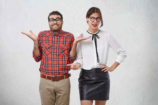 厚いレンズの肩をすくめる、四角い眼鏡をかけた不屈の男性、ためらいがあり、イライラした女性が彼を見ている 無料写真