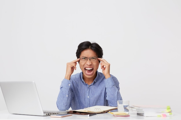 Irritated asian young business man in glasses with mouth opened touching temples and shouting sitting at the table over white wall Free Photo