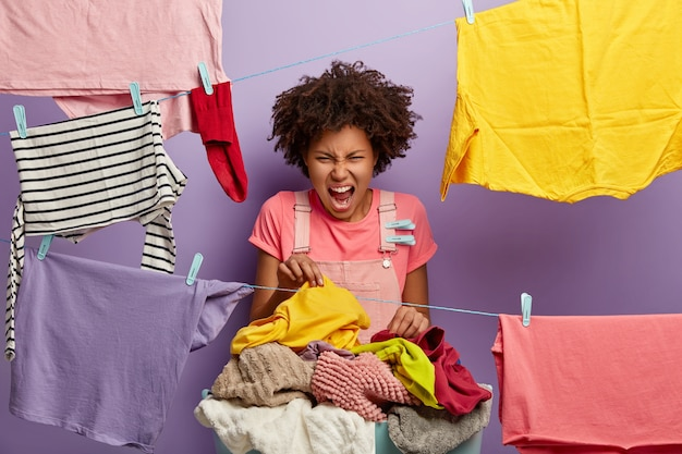 Irritated curly haired housewife screams with annoyance, picks up dirty linen with unpleasant stench, busy doing washing at home during weekend, surroundeed by hanged wet clean clothes on rope Free Photo