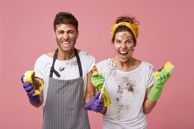 Uomo e donna irritati dal servizio di pulizia che indossano vestiti sporchi che tengono attrezzature per la pulizia aggrottando le sopracciglia essendo occupati con la pulizia guardando mobili in disordine con disgusto e rabbia Foto Gratuite