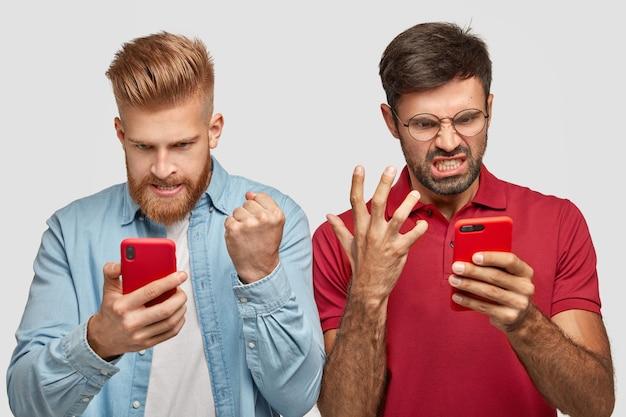 Due ragazzi irritati guardano con rabbia lo schermo degli smartphone, guardano la partita di calcio online, sono infastiditi perché la squadra preferita ha perso la partita, concentrati su qualcosa, vestiti con abiti alla moda, posa al coperto Foto Gratuite