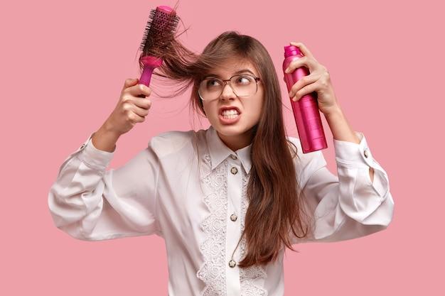 Раздраженная барышня делает прическу лаком и расческой, у нее растрепанные волосы Бесплатные Фотографии