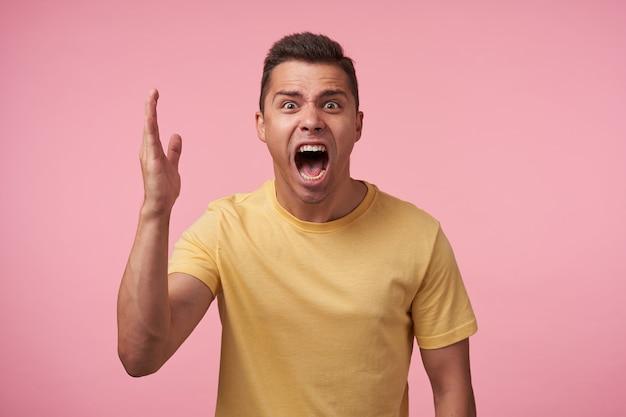 Irritato giovane uomo dai capelli corti bruna con taglio di capelli corto urlando crossly con ampia bocca aperta e sollevando emotivamente il palmo mentre posa su sfondo rosa Foto Gratuite
