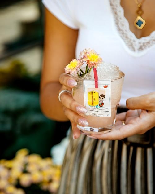 Женщина держит стакан напитка со льдом, украшенный вкладышем от любви isgum Бесплатные Фотографии