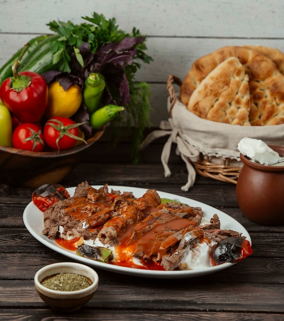 Iskender kebab garnished with tomato sauce and yoghurt, served with grilled vegetables Free Photo