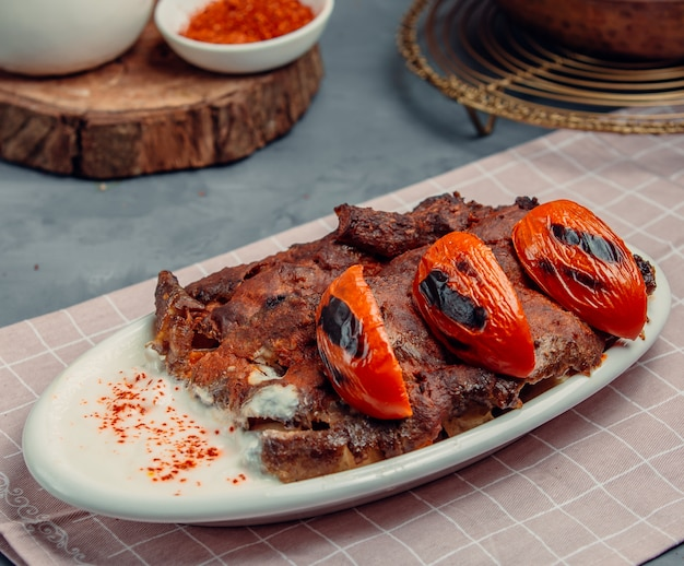 Iskender kebab with fried tomatoes Free Photo