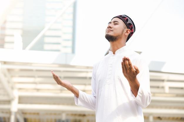 Islam muslim young men praying outdoor in city background Premium Photo