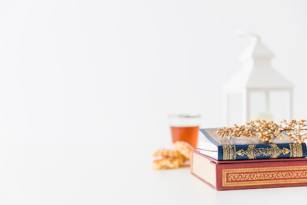 Islamic books with lantern and branch Free Photo