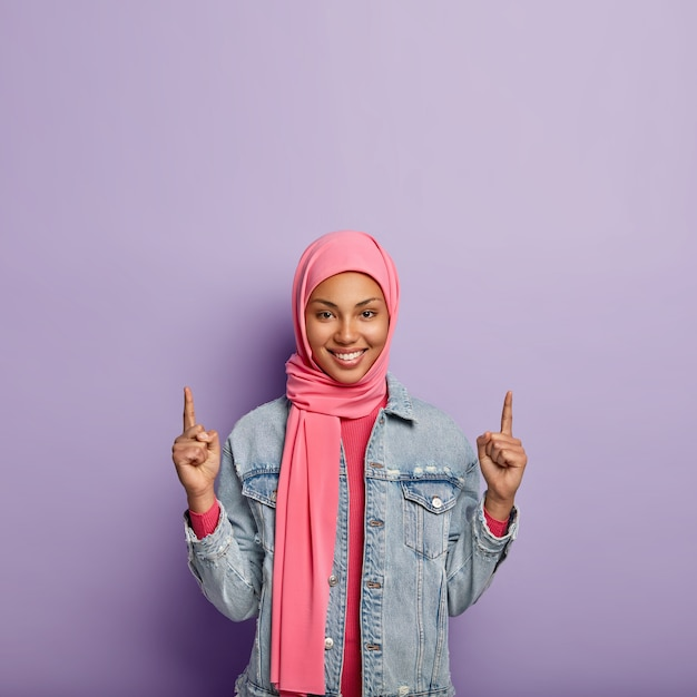 Islamic fashion concept. glad positive female with specific appearance and clothes, points above on free space, shows something upwards, wears fashionabe jacket. girl in hijab advertises object up Free Photo