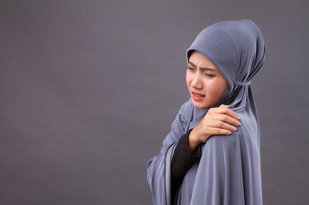 Islamic muslim woman with shoulder or neck pain, stiffness, injury Premium Photo