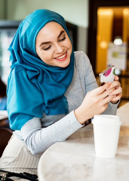Islamic woman using smart phone and smiling Free Photo