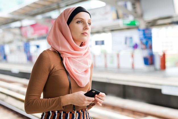 Islamic woman waiting for sky train Premium Photo