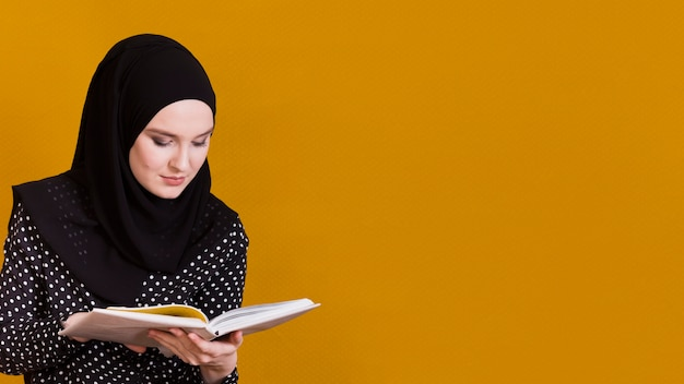 Islamic woman with headscarf reading book in front of background with copy space Premium Photo