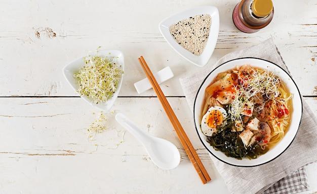 白い木製のテーブルの上にボウルにキャベツキムチ、海藻、卵、マッシュルーム、チーズ豆腐と味isoラーメンアジア麺。 無料写真