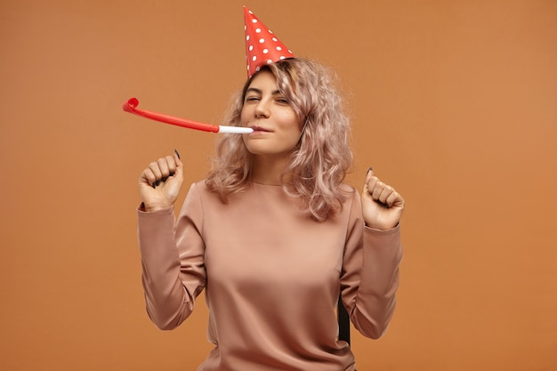 Isolated of attractive cheerful happy young woman wearing stylish top and red cone cap blowing whistle and dancing, having overjoyed facial expression, celebrating her birthday Free Photo
