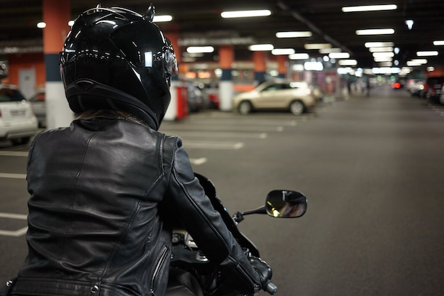 Isolated back view of female biker driving two wheeled sportbike along underground paking lot hallway, going to park her motorcycle after night ride. motorcycling, extreme sports and lifestyle Free Photo