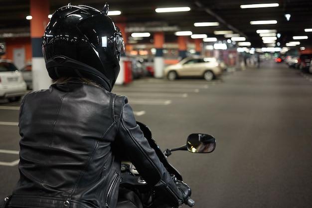 地下の舗装区画の廊下に沿って二輪のスポーツバイクを運転し、夜の乗車後にバイクを駐車する女性バイカーの孤立した背面図。モーターサイクル、エクストリームスポーツ、ライフスタイル 無料写真