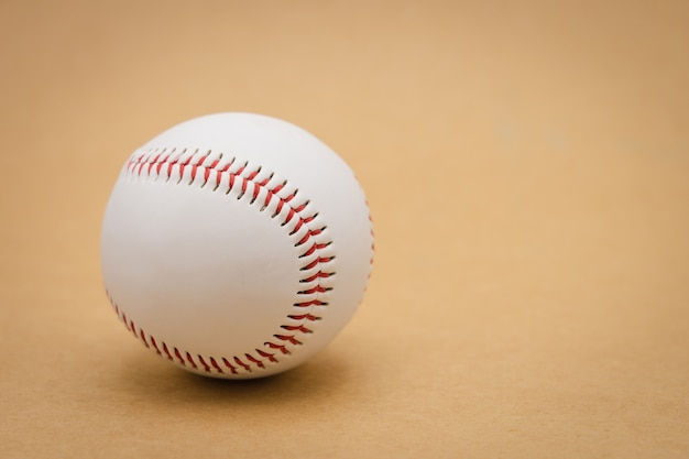 Isolated baseball on a brown background and red stitching baseball. white baseball Premium Photo