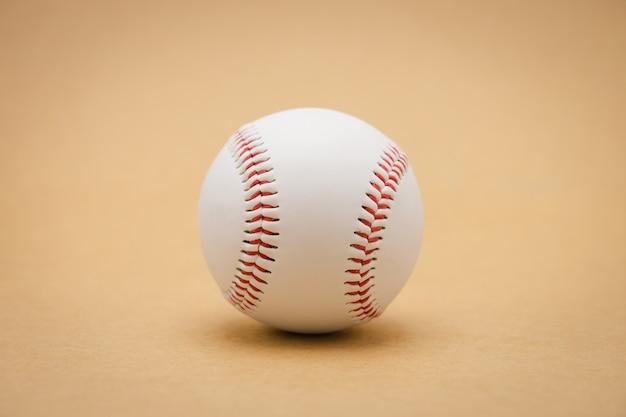 Isolated baseball on a brown background and red stitching baseball. white baseball Premium Photo