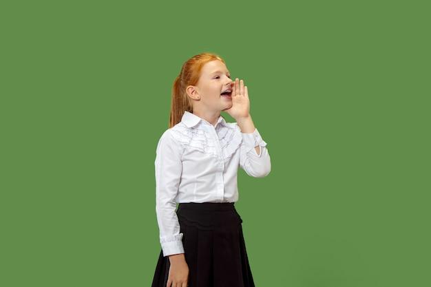 Isolato su verde giovane ragazza adolescente casual gridando in studio Foto Gratuite
