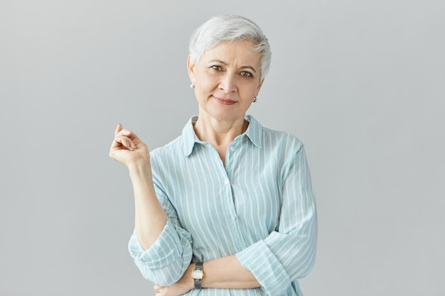 Isolated image of elegant fashionable middle aged european woman on retirement posing  wearing stylish striped blue shirt and wrist watch, having good day, smiling  happily Free Photo