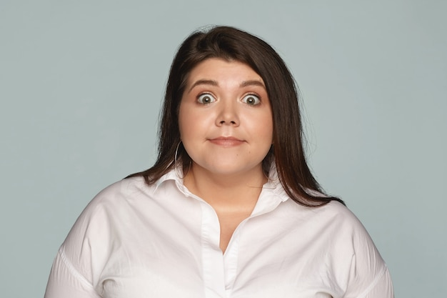 Isolated image of funny buy eyed plus size female manager in white formal shirt expressing astonishment, staring in full disbelief, shocked with unexpected news or gossip. surprise and shock Free Photo