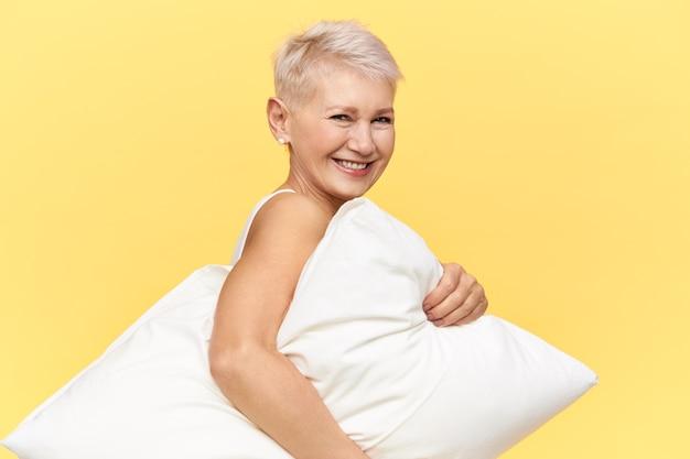Mulher idosa sorrindo segurando travesseiro. (HORAS DORMIDAS)