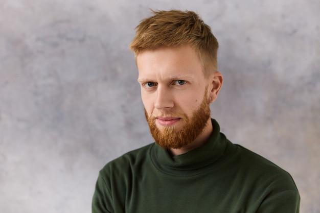 強烈な集中した表情で見つめているエレガントなスタイリッシュな服を着た魅力的な赤い髪のひげを生やした若い白人男性の孤立した画像。人間の表情と態度 無料写真