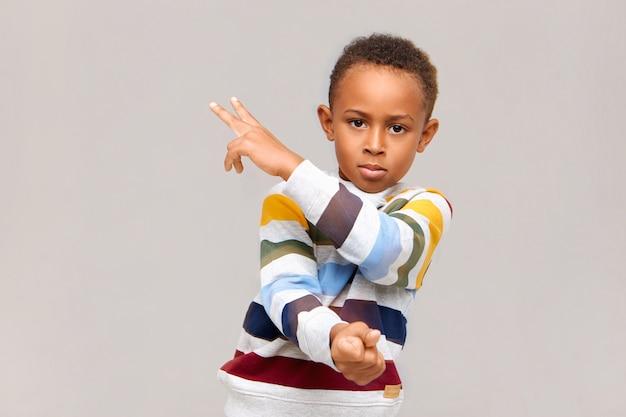 Изолированное изображение уверенно красивого афро-американского мальчика, носящего полосатый джемпер, жестикулирующего на глухую стену, показывая два знака пальцами, глядя прямо с серьезным взглядом Бесплатные Фотографии