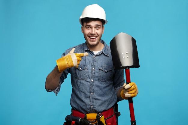 Изолированное изображение эмоционального веселого молодого обслуживающего работника в спецодежде, глядя на камеру Бесплатные Фотографии