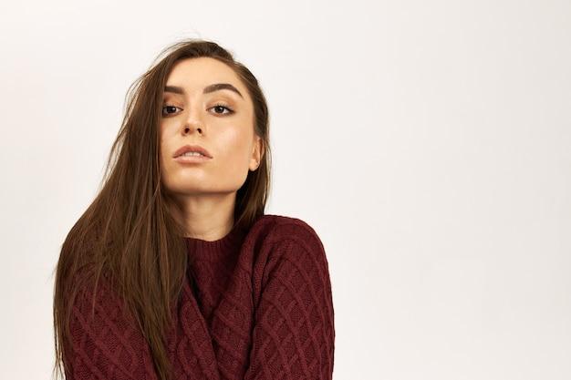 복사 공간 흰색 스튜디오 벽 배경에 포즈 니트 스웨터에 워밍업 긴 Borwn 머리를 가진 좋은 찾고 아름 다운 젊은 여자의 고립 된 이미지 무료 사진