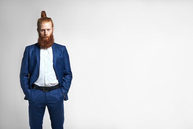 성공적인 유행 젊은 사업가 머리 매듭과 유행 수염을 가진 심각한 자신감 모습, 그의 세련 된 옷 주머니에 양손을 유지의 고립 된 이미지. 성공과 경력 무료 사진
