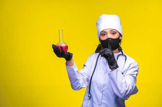 Isolated nurse in hand and face mask holds chemical flask and makes point to danger Free Photo