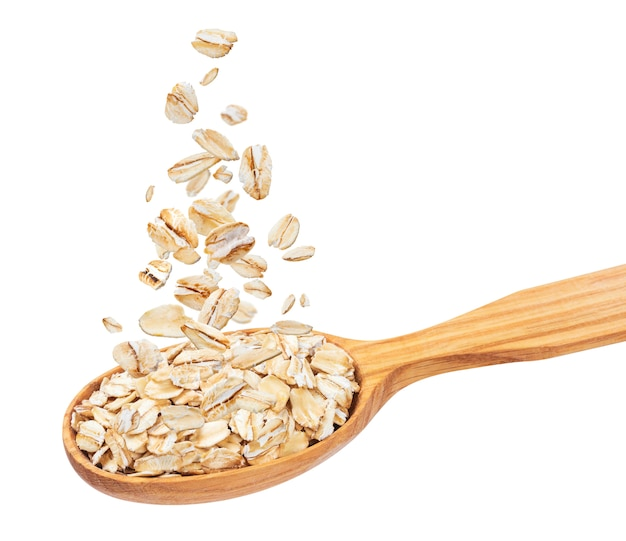 Isolated oatmeal, oat flakes in spoon Premium Photo