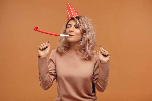 スタイリッシュなトップと赤いコーンキャップを身に着けて笛を吹いて踊り、表情を大喜びし、彼女の誕生日を祝って、魅力的な陽気な幸せな若い女性の孤立 無料写真