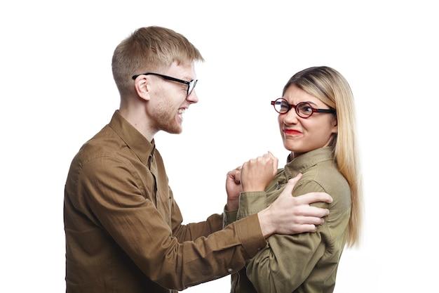 Изолированная картина сердитой модной молодой пары мужчина и женщина в рубашках и очках, имеющих бой. раздраженный бородатый мужчина тряс девушку за плечи Бесплатные Фотографии