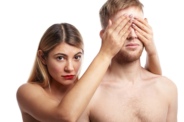 Isolated picture of two lovers posing naked: attractive blonde woman with tanned smooth skin and facial piercing covering eyes of her bearded boyfriend and staring with shy look Free Photo