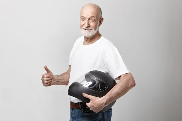 Isolated picture of white senior unshaven european male in casual t-shirt holding motorcycle helmet Free Photo