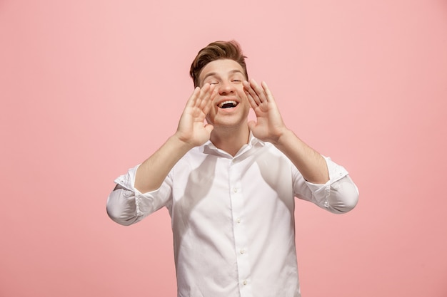 Isolated on pink young casual man shouting at studio Free Photo
