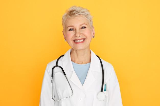 Изолированный портрет уверенно опытной женщины-врача среднего возраста с короткой светлой стрижкой, смотрящей с счастливой улыбкой Бесплатные Фотографии