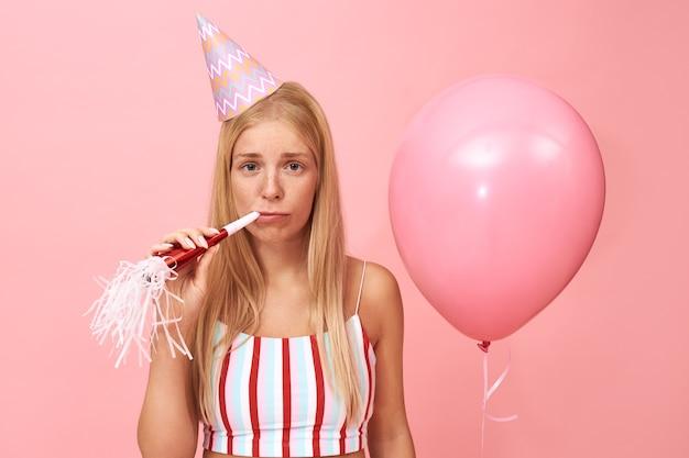 Изолированные портрет расстроенной грустной молодой европейской женщины в конической шляпе и летнем топе, празднующем день рождения, с расстроенным лицом, выражающим дует рожок для вечеринки Бесплатные Фотографии