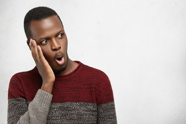 Isolated portrait of shocked young afro-american male in casual sweater looking in full disbelief, hand on cheek, surprised with some astonishing news. human emotions, feelings, attitude, reaction Free Photo