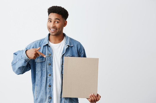 Isolated portrait of young good-looking dark-skinned male with afro hairstyle in white t-shirt under denim jacket holding paper board in hand, pointing at it with happy and enthusiastic expression Free Photo