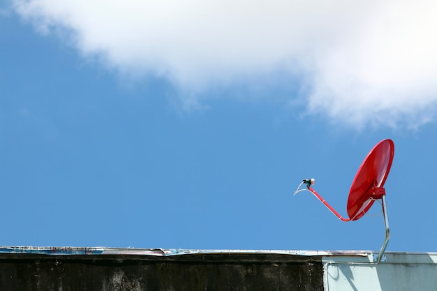 Isolated red satellite on sunny blue sky Premium Photo