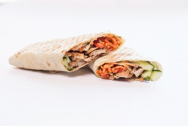Isolated shawarma with a shadow. oriental food made from chicken meat, tomatoes, cucumbers in pita bread Premium Photo
