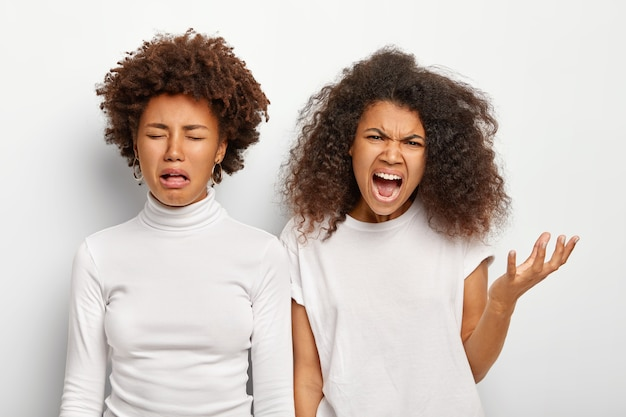 Colpo isolato di due sorelle etniche scontente arrabbiate hanno fallito, urlano con rabbia Foto Gratuite