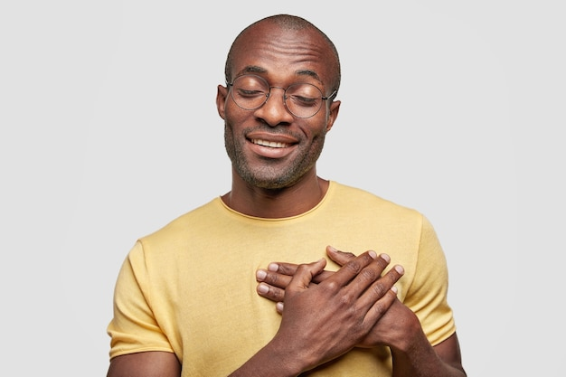 Isolated shot of delighted african american male with cheerful expression Free Photo
