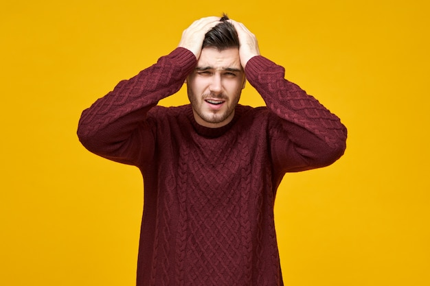 Isolated shot of frustrated young male in knitted pullover keeping hands on head and grimacing suffering from migraine because of stressful work, having painful facial expression, feeling unwell Free Photo